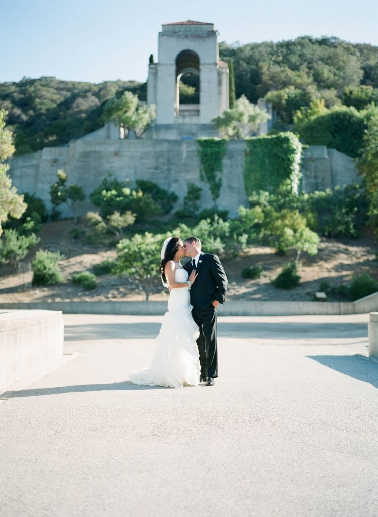 bride and groom kissing with wrigley memorial in background catalina island