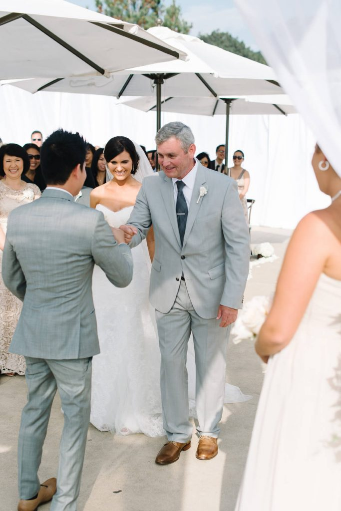 father of bride fist bumping groom at altar