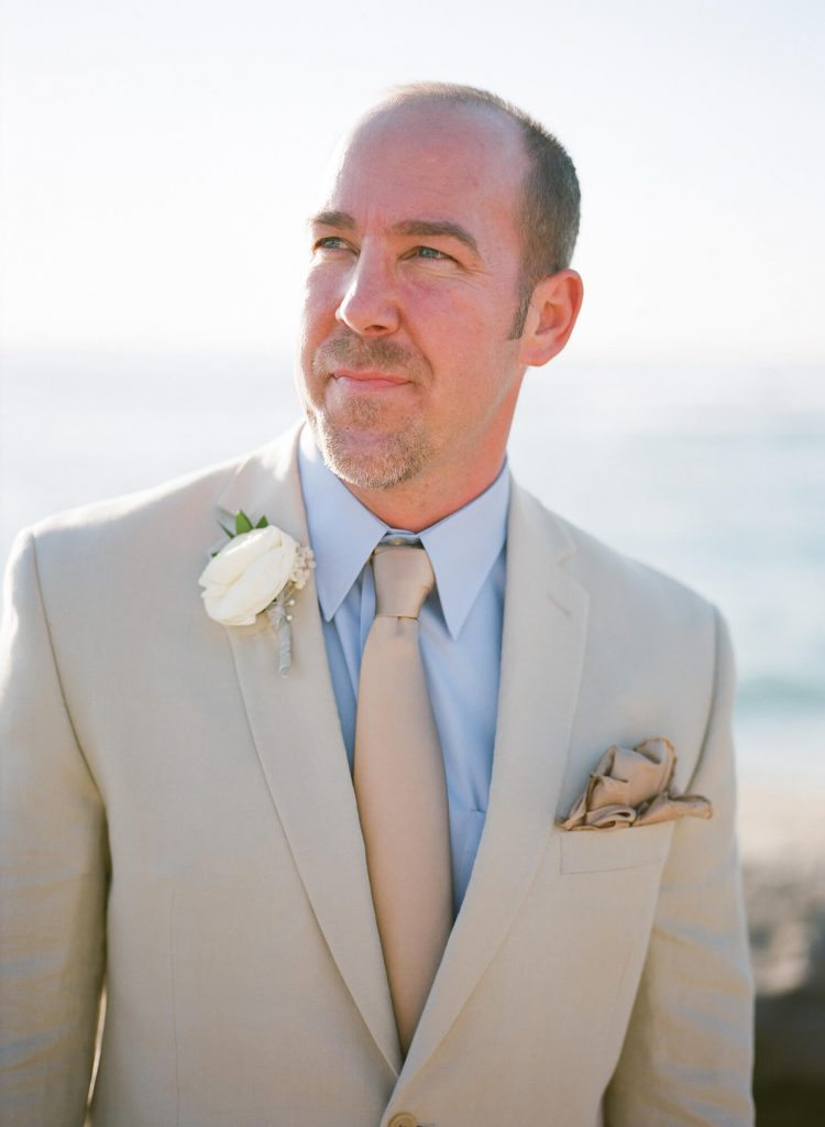 groom in tan suit and blue shirt and beige tie intimate beach wedding