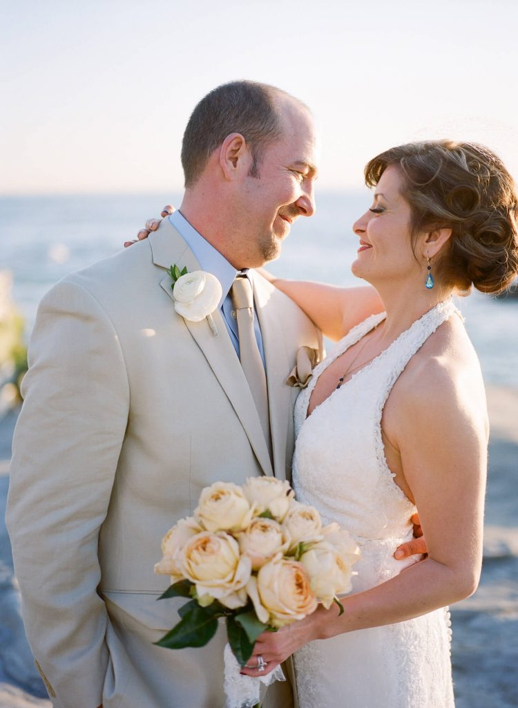 bride and groom embrace sunset intimate beach wedding