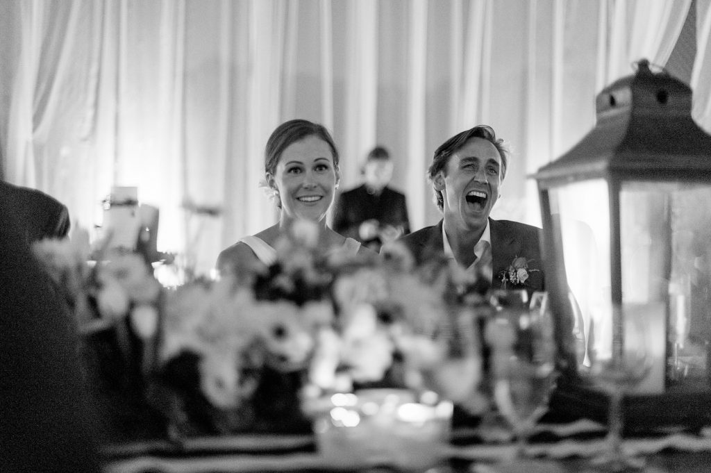 bride and groom laugh during speech