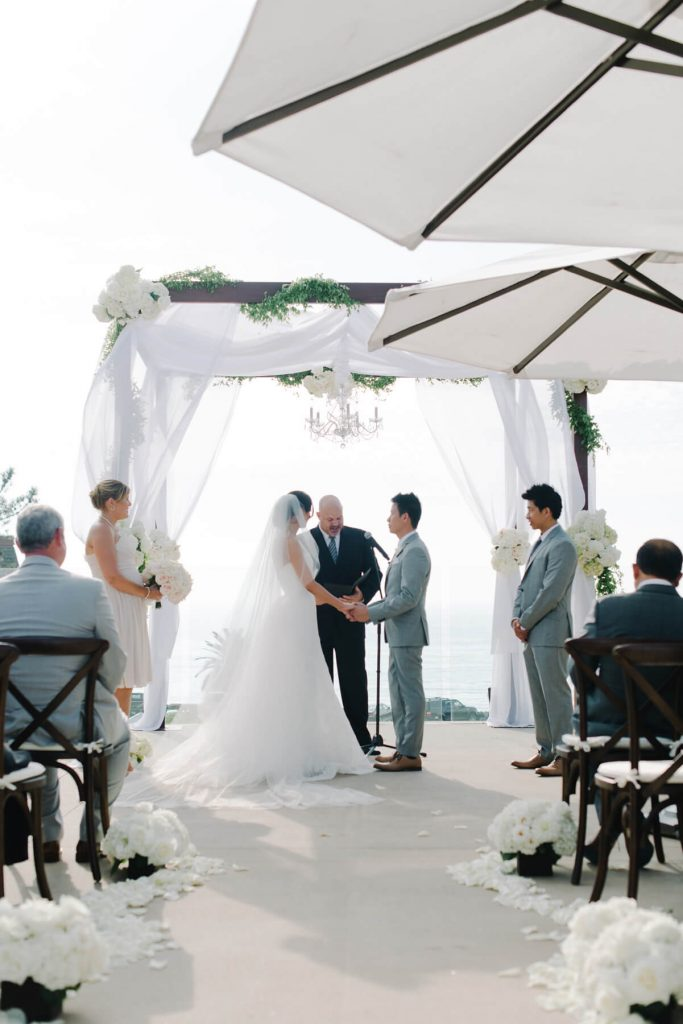 bride and groom ceremony under wooden arch with tule pacific terrace lauberge wedding del mar