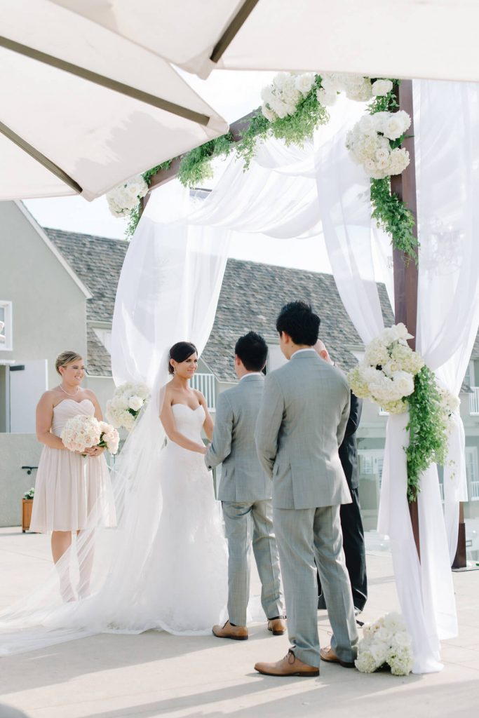 bride and groom ceremony under wooden arch with tule pacific terrace lauberge hotel
