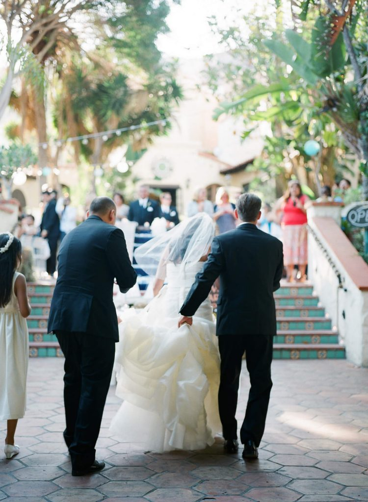 groom and groomsman help bride up stairs grand entrance catalina island wedding reception