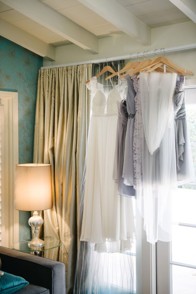 brides gown and bridesmaid dresses hanging in hotel suite