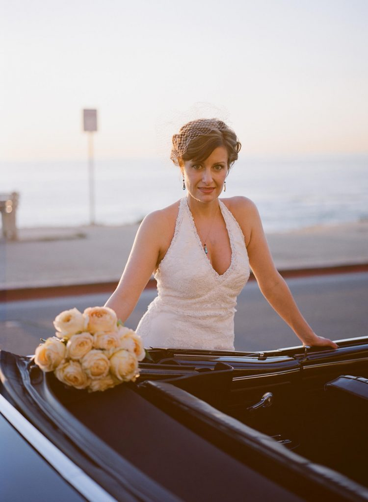 bride in vintage gown and birdcage veil with bouquet of double roses on getaway car