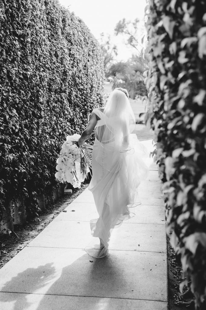 bride walking and carrying dress and veil