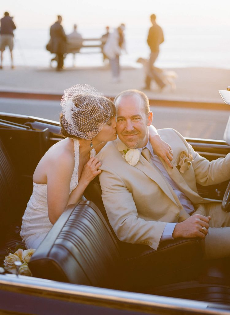 bride in vintage gown and birdcage veil sits in back seat and gives groom kiss on cheek