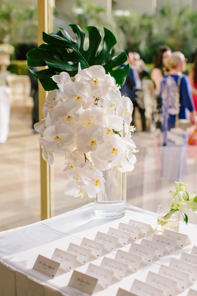 vase with white orchids on table with escort cards