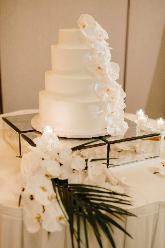 four tier white wedding cake with white orchids and palm leaves