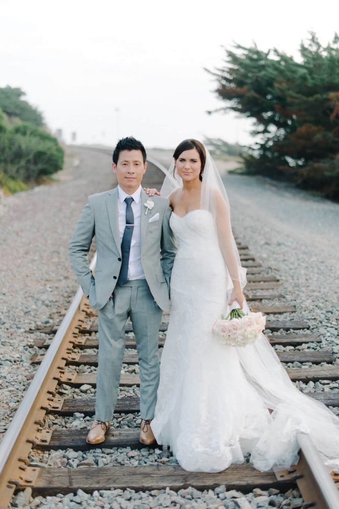 bride and groom posing on train tracks in del mar san diego beach wedding