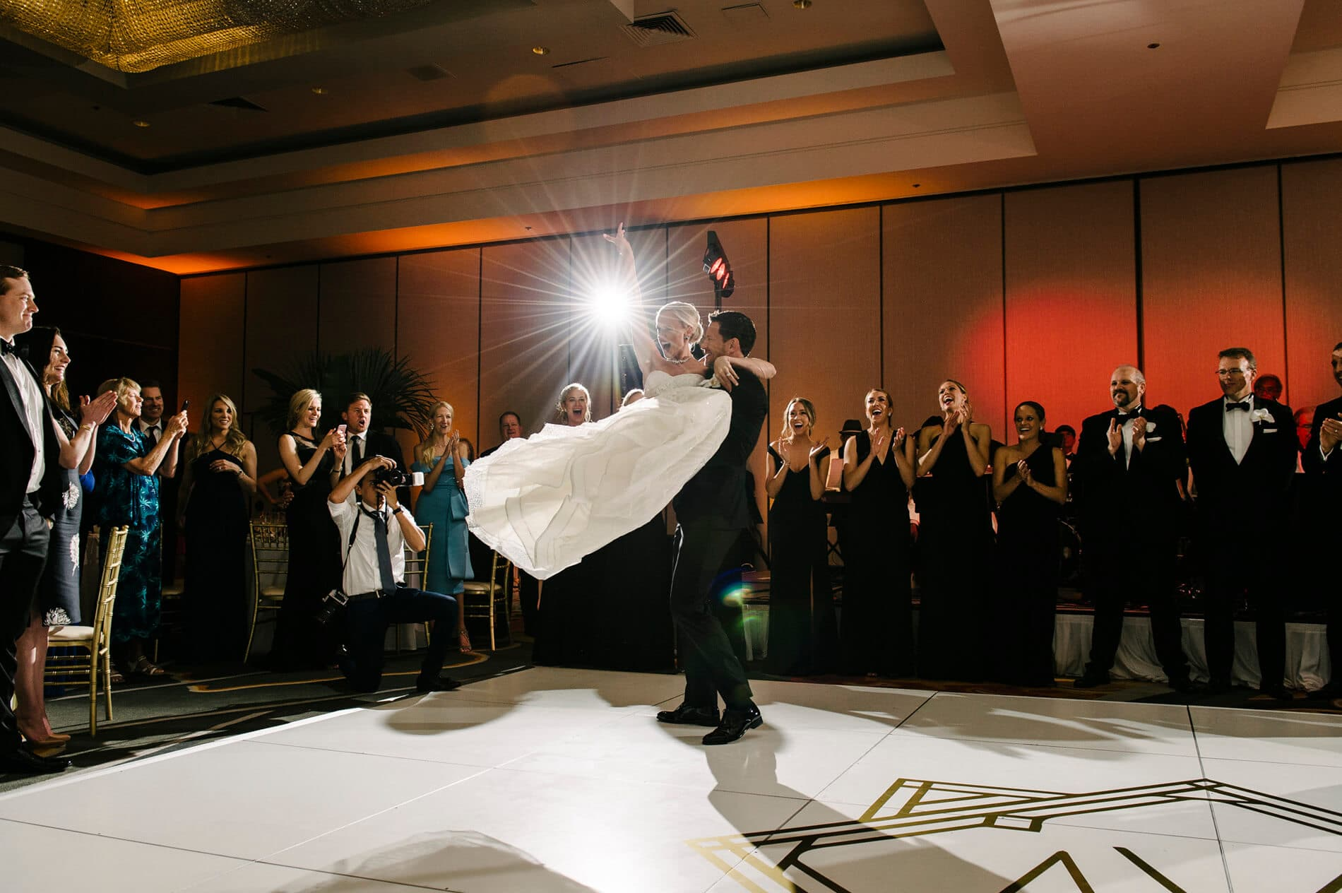 groom picking up bride and spinning on dance floor at hilton la jolla torrey pines