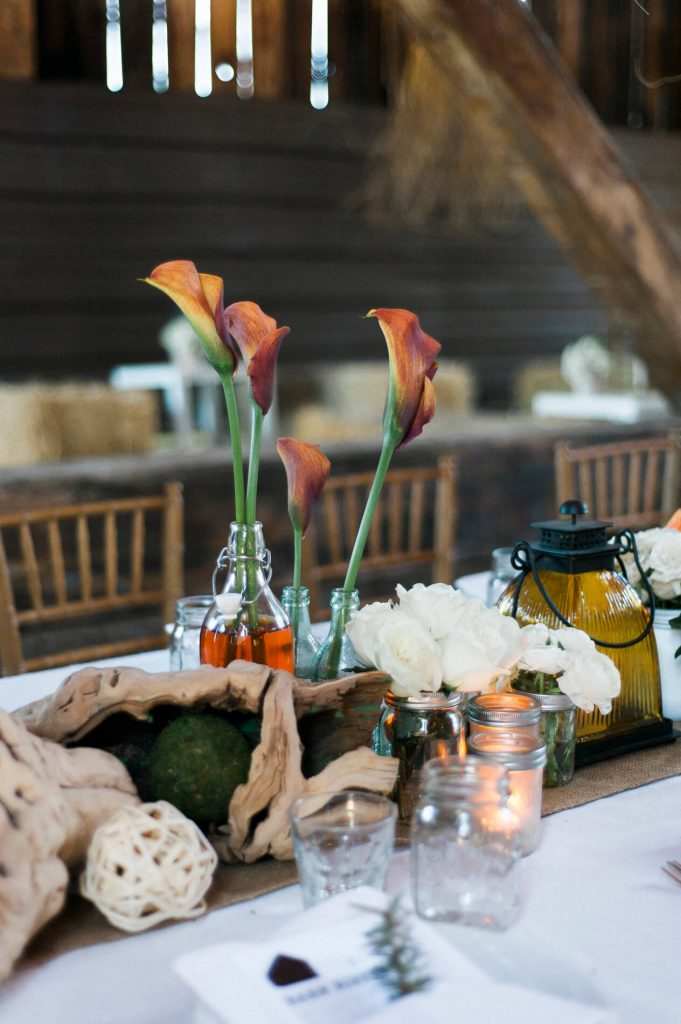 orange calla lilies and white roses in mason jars on table at rustic barn wedding in lake almanor