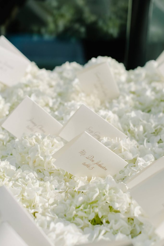 escort cards sitting in white flowers san diego beach wedding