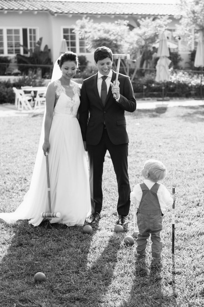 bride and groom holding croquet mallets with young boy inn at rancho santa fe wedding