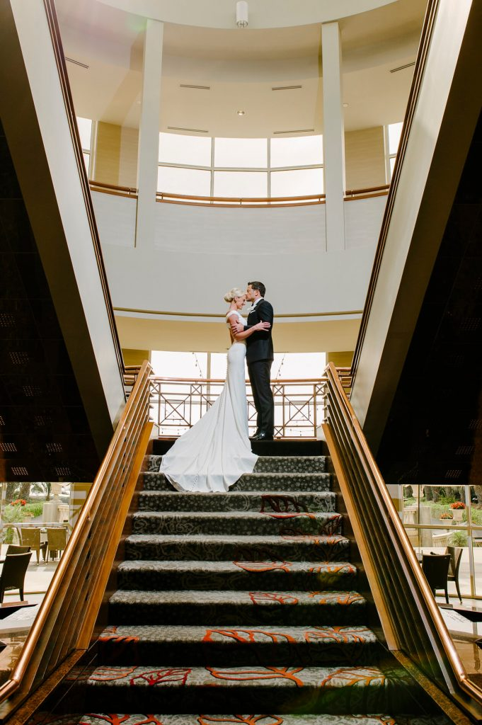 bride and groom kissing at top of stairs inside lobby of hilton la jolla torrey pines