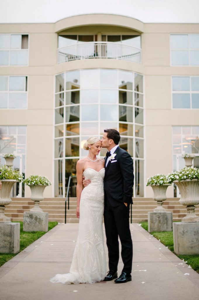 bride and groom kissing in front of hilton la jolla torrey pines