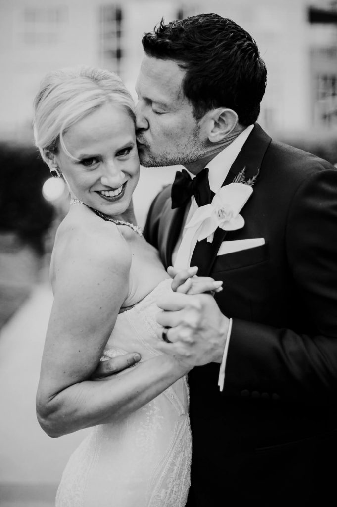 groom kissing bride black and white