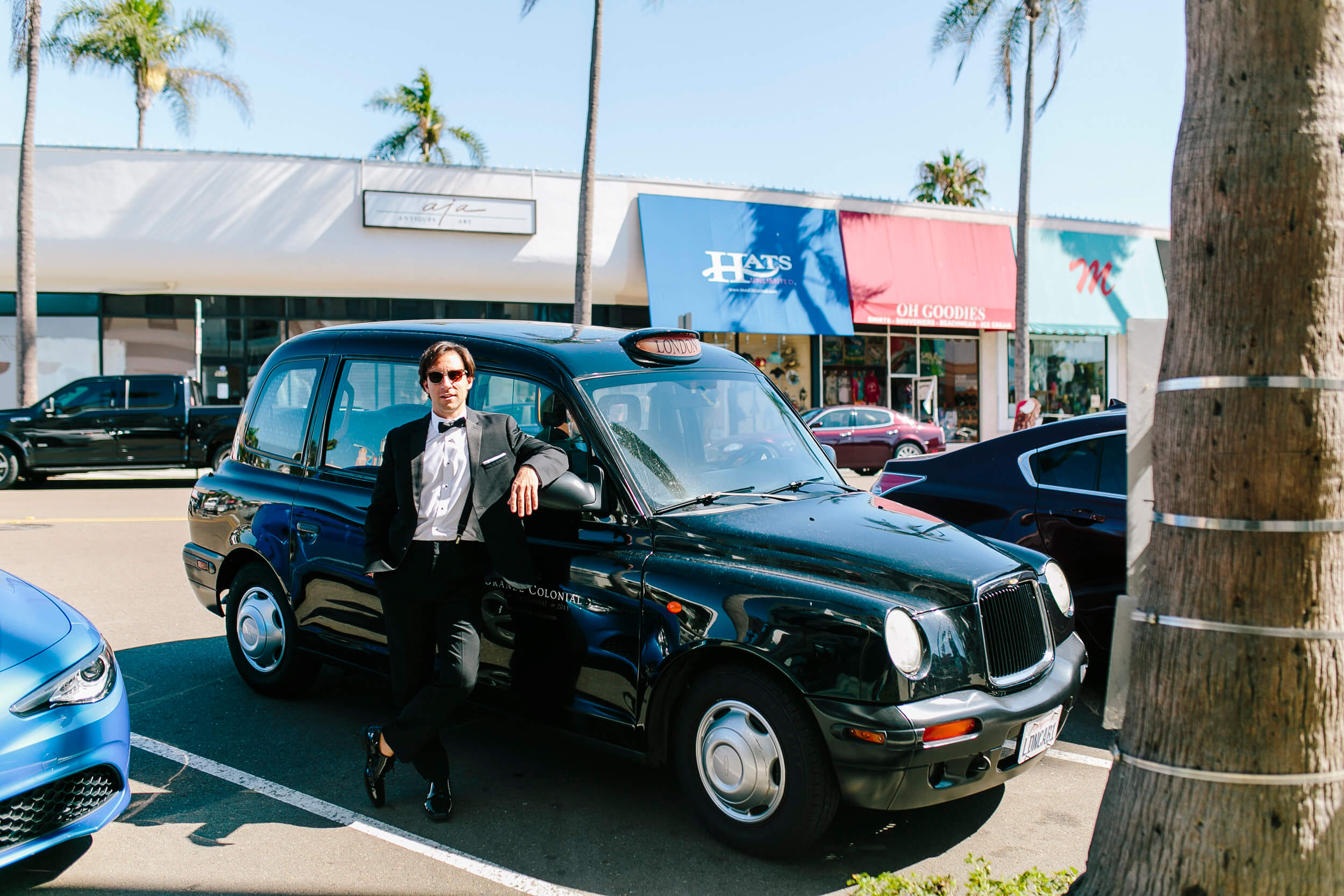 groom poses with vintage english taxi grande colonial hotel la jolla