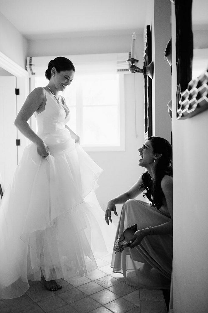 bridesmaid and bride laugh as bride puts on shoe