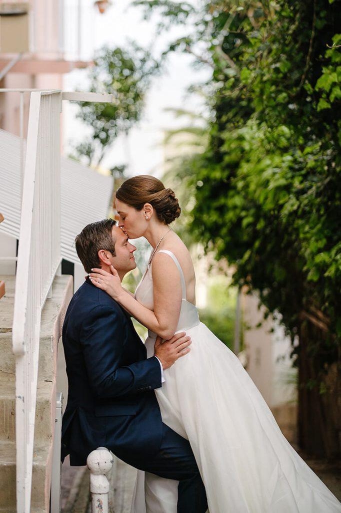bride and groom pose on walkway next to la valencia hotel