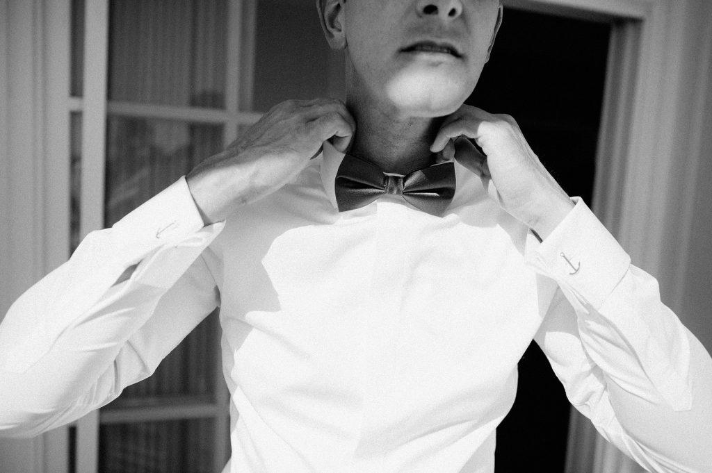 groom putting on bowtie