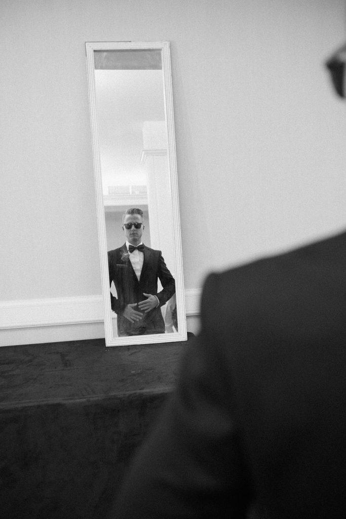 groom putting on tuxedo in mirror hotel del coronado