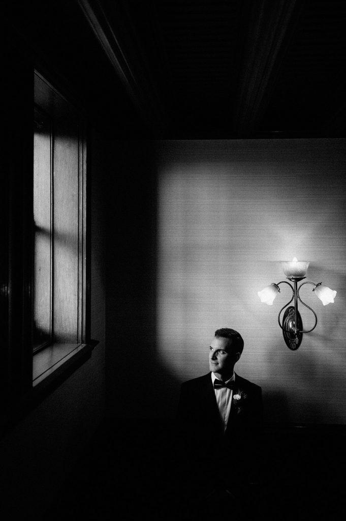 groom posing hotel del coronado same sex wedding