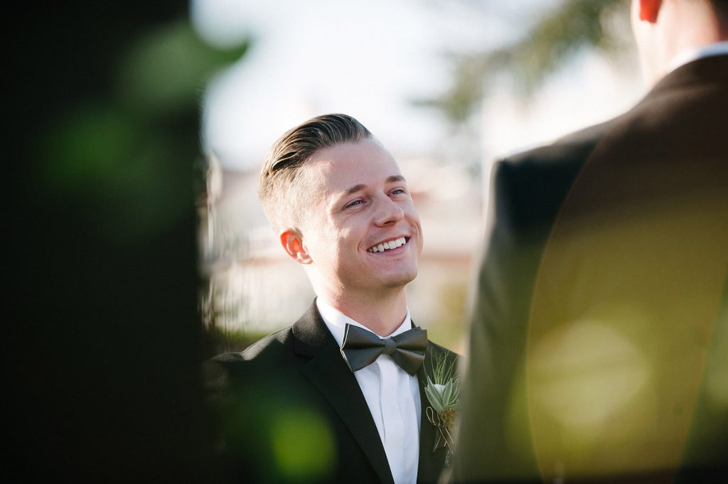 groom smiling at husband same sex wedding