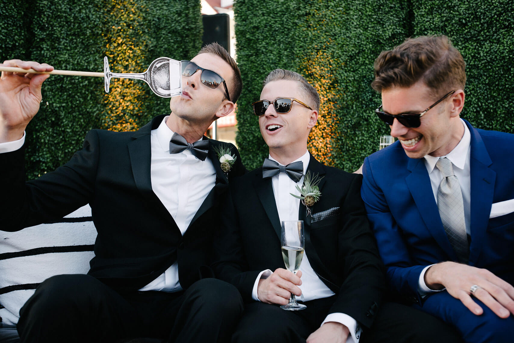 two grooms and guest laughing and drinking champagne