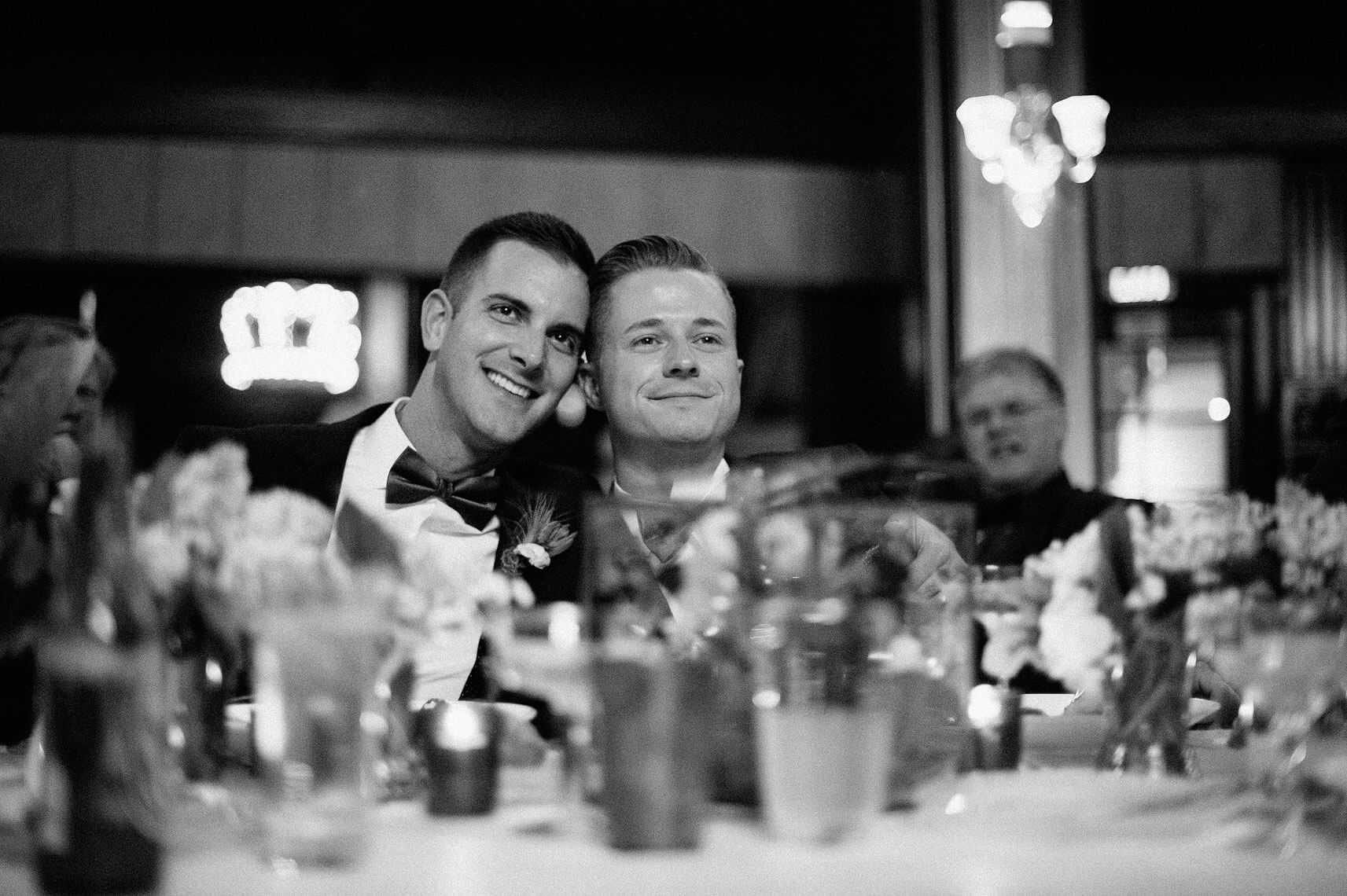 two grooms with heads together listening to speeches