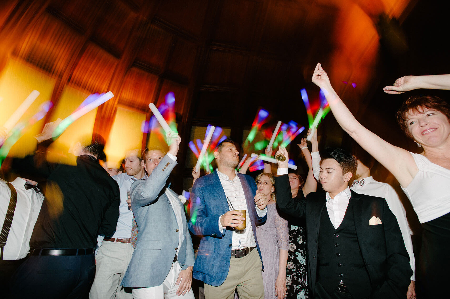 guests dance with glow sticks at same sex wedding