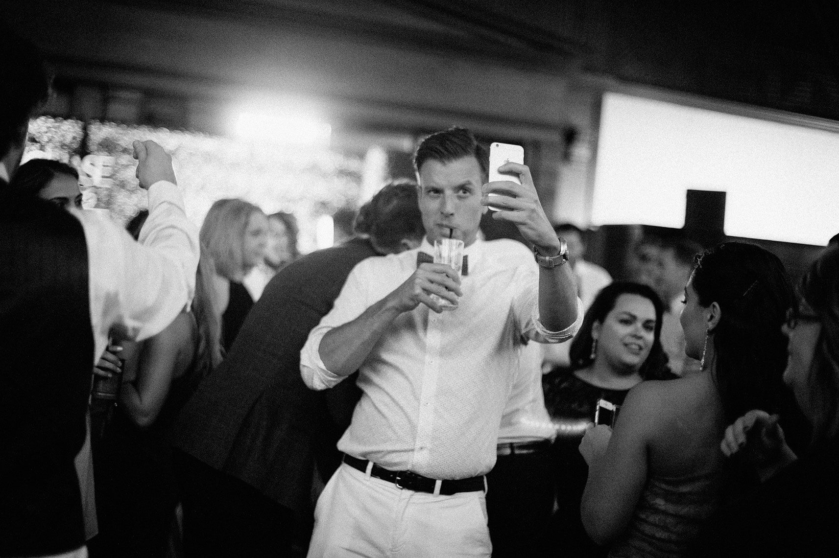 guest takes selfie with cocktail same sex wedding