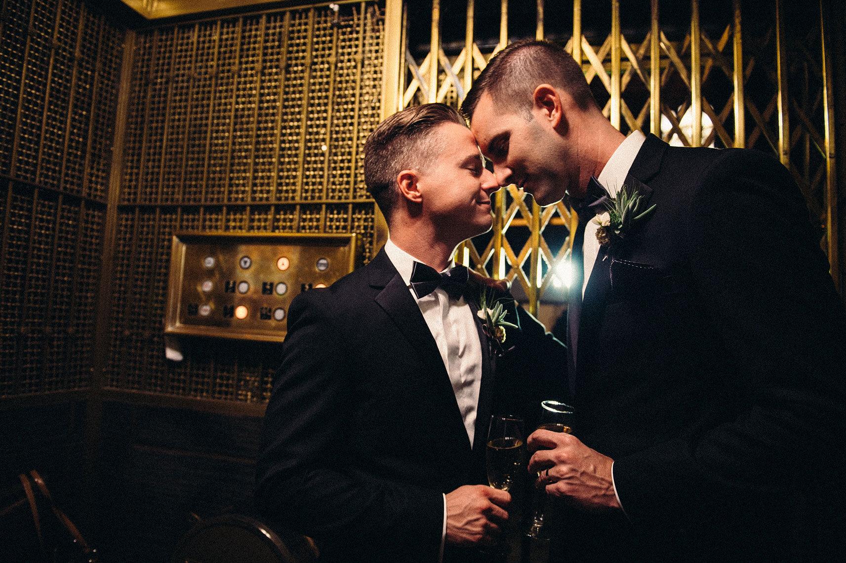 two grooms embracing in vintage elevator same sex wedding hotel del coronado