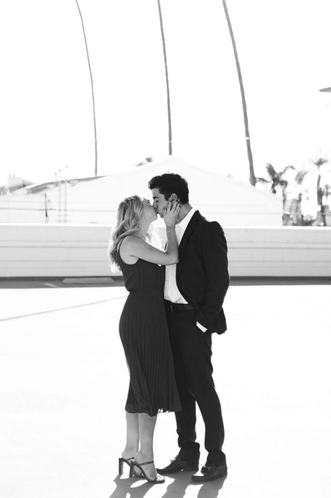 woman in long dress and man in dark suit kiss on rooftop in downtown la jolla romantic engagement photo