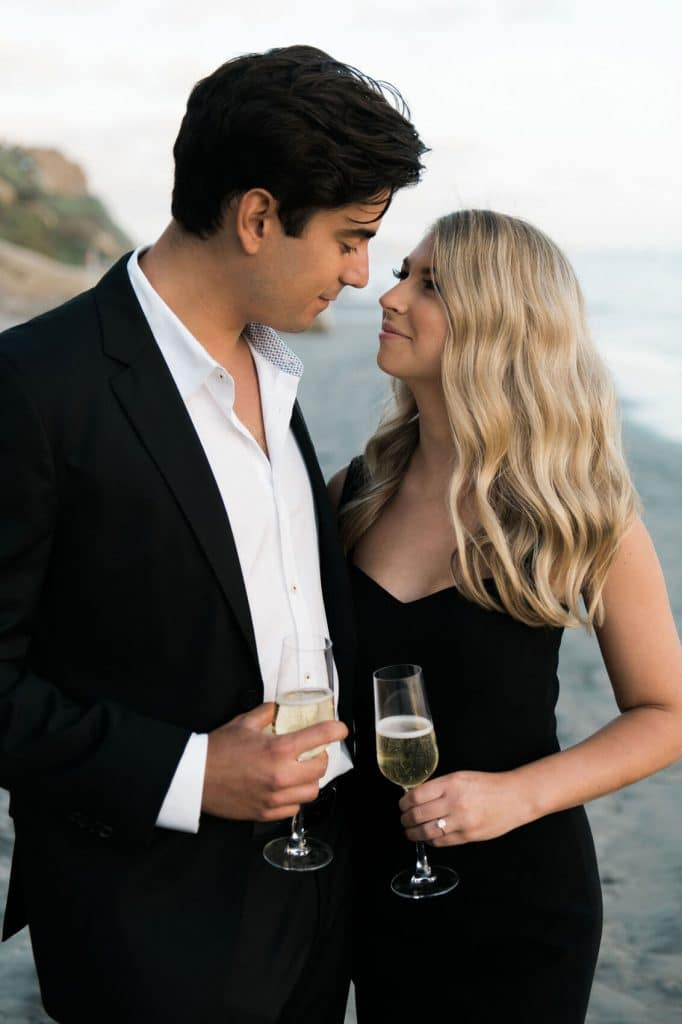 man in dark suit and woman in black cocktail dress drink champagne on beach during del mar beach engagement photos