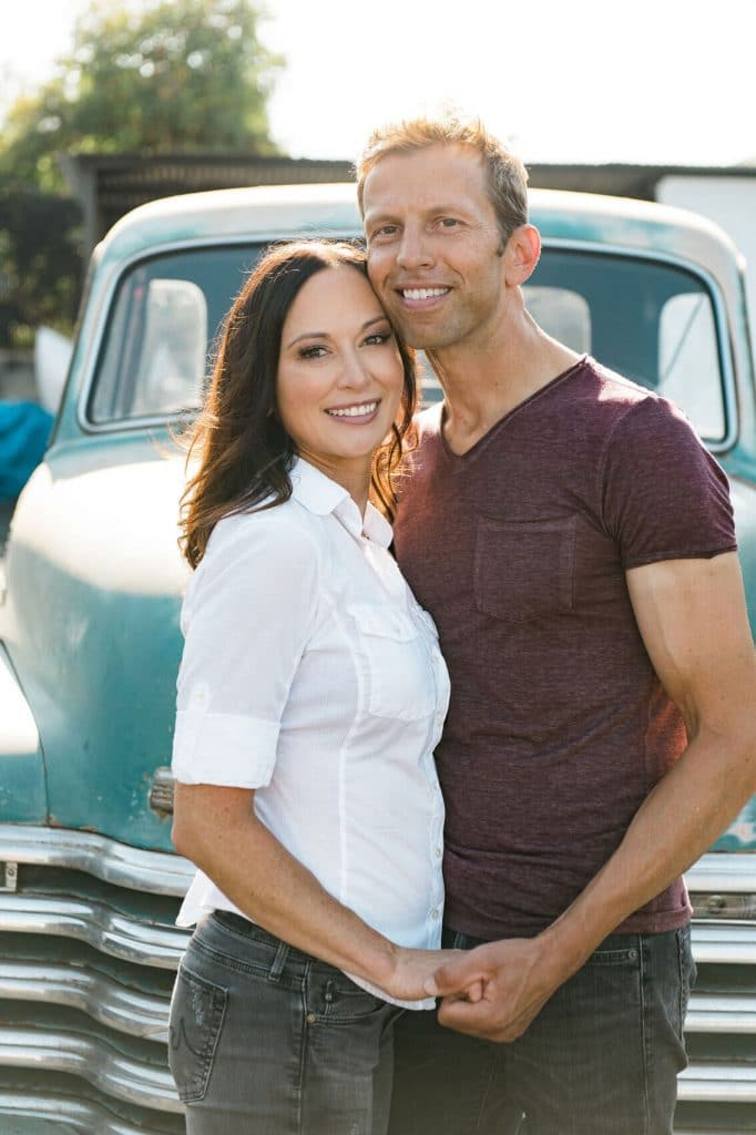 couple embracing in front of blue vintage pickup truck
