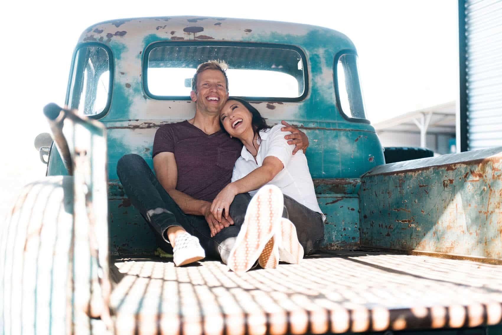 couple laughing in bed of vintage pickup truck industrial engagement photo session