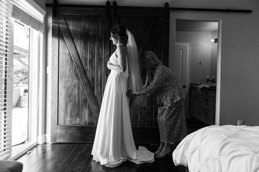 mother helping bride with dress before intimate wedding in oakhurst