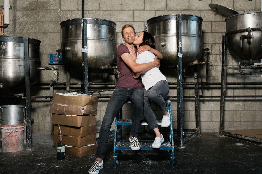 couple embracing in front of vats of melted surf wax industrial engagement photo session