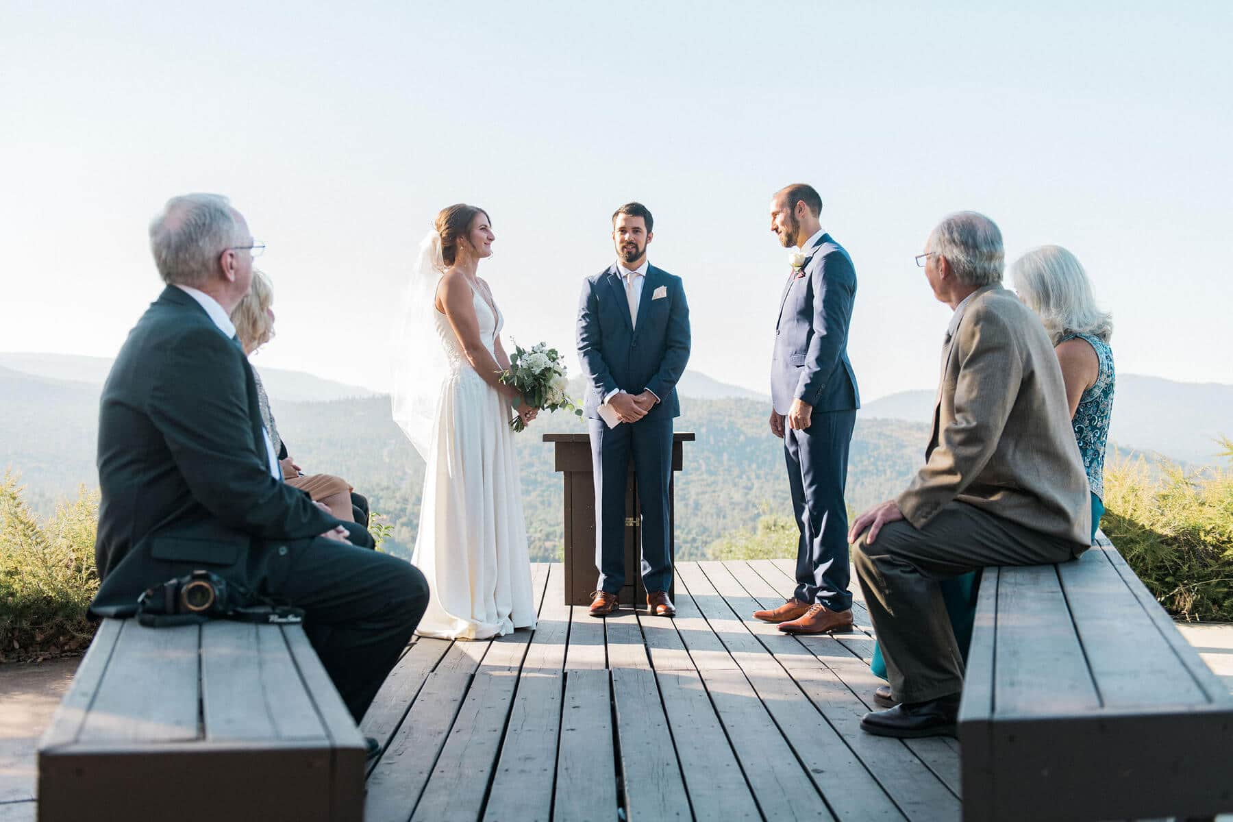 bride and groom standing on deck during intimate ceremony in oakhurst