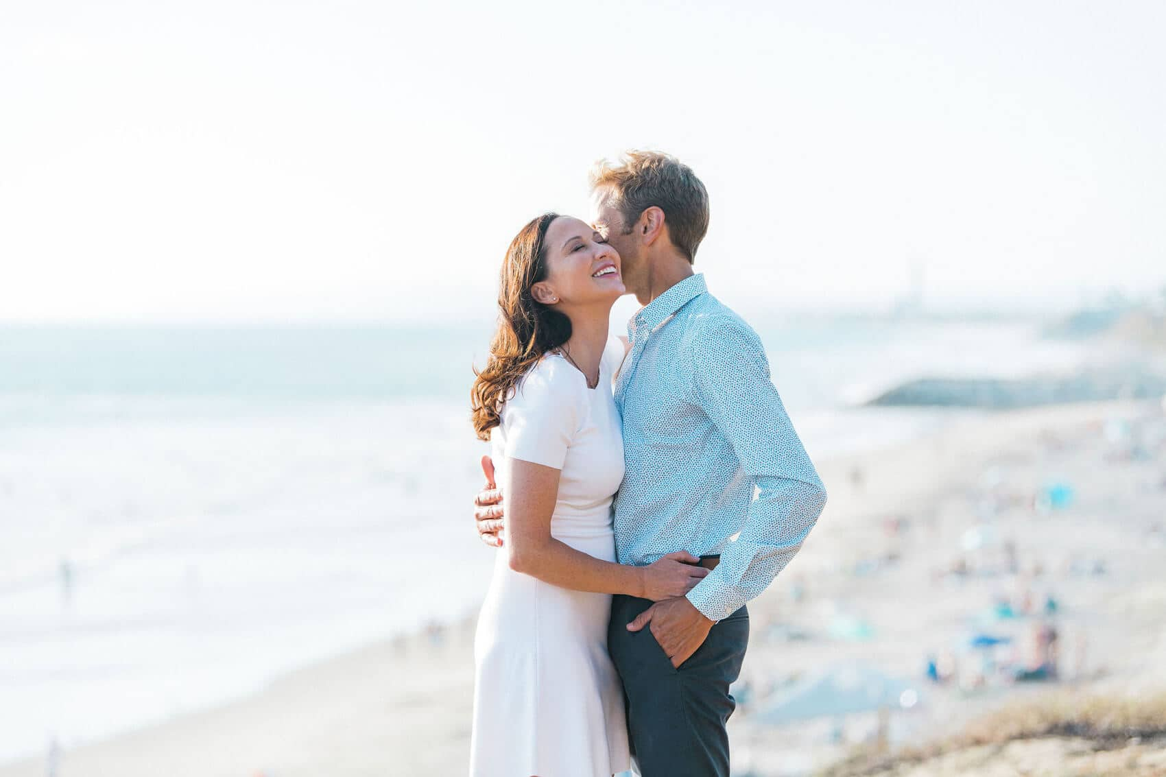 couple embracing and laughing high above ponto beach in carlsbad california