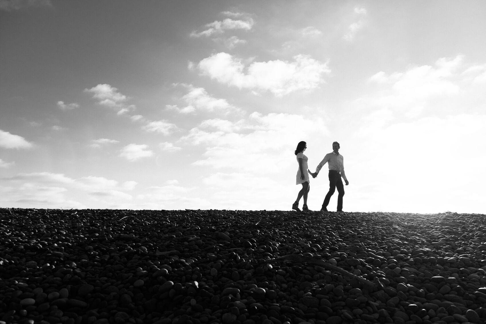 couple walking holding hands ponto beach engagement photo