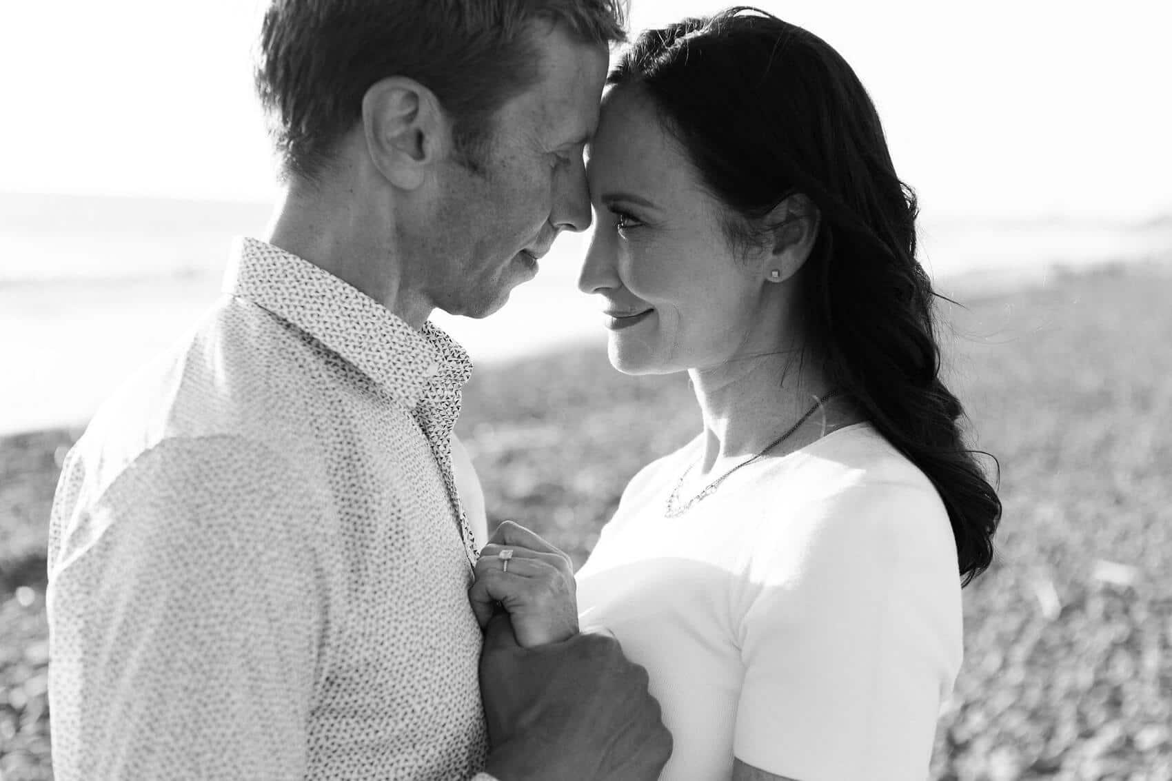 couple embracing on cobblestone beach ponto carlsbad engagement photo