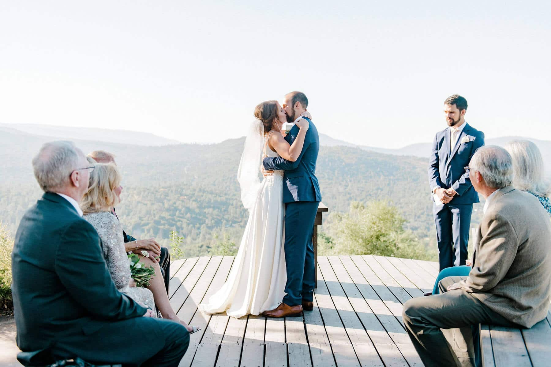 bride and groom kissing on balcony during intimate wedding ceremony in oakhurst