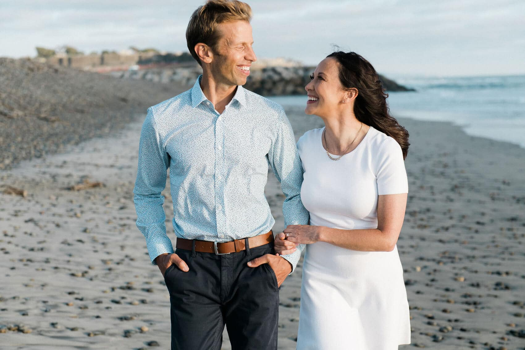 couple walking on rocky beach ponto engagement photos carlsbad