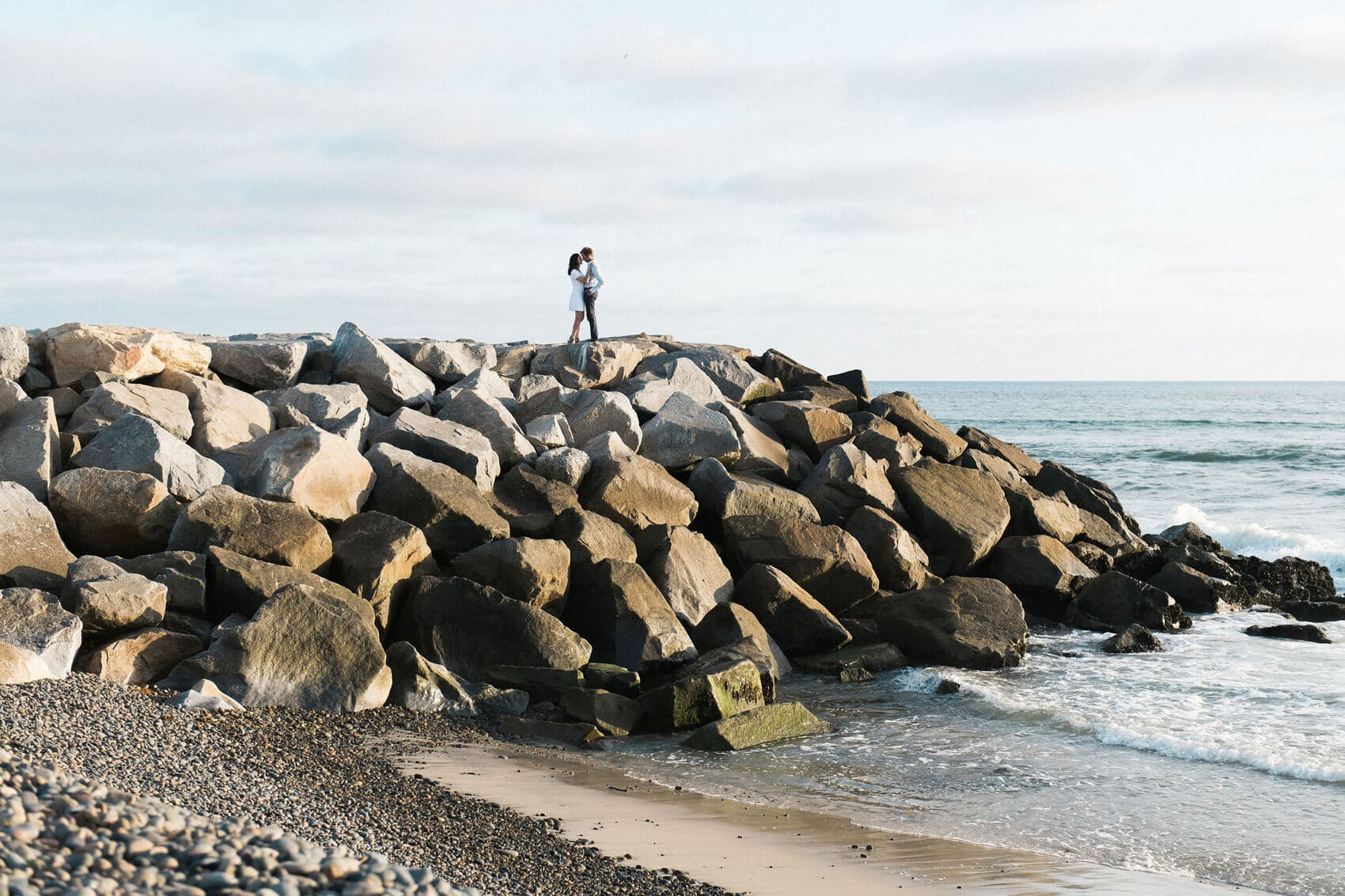 couple embracing on jetty carlsbad