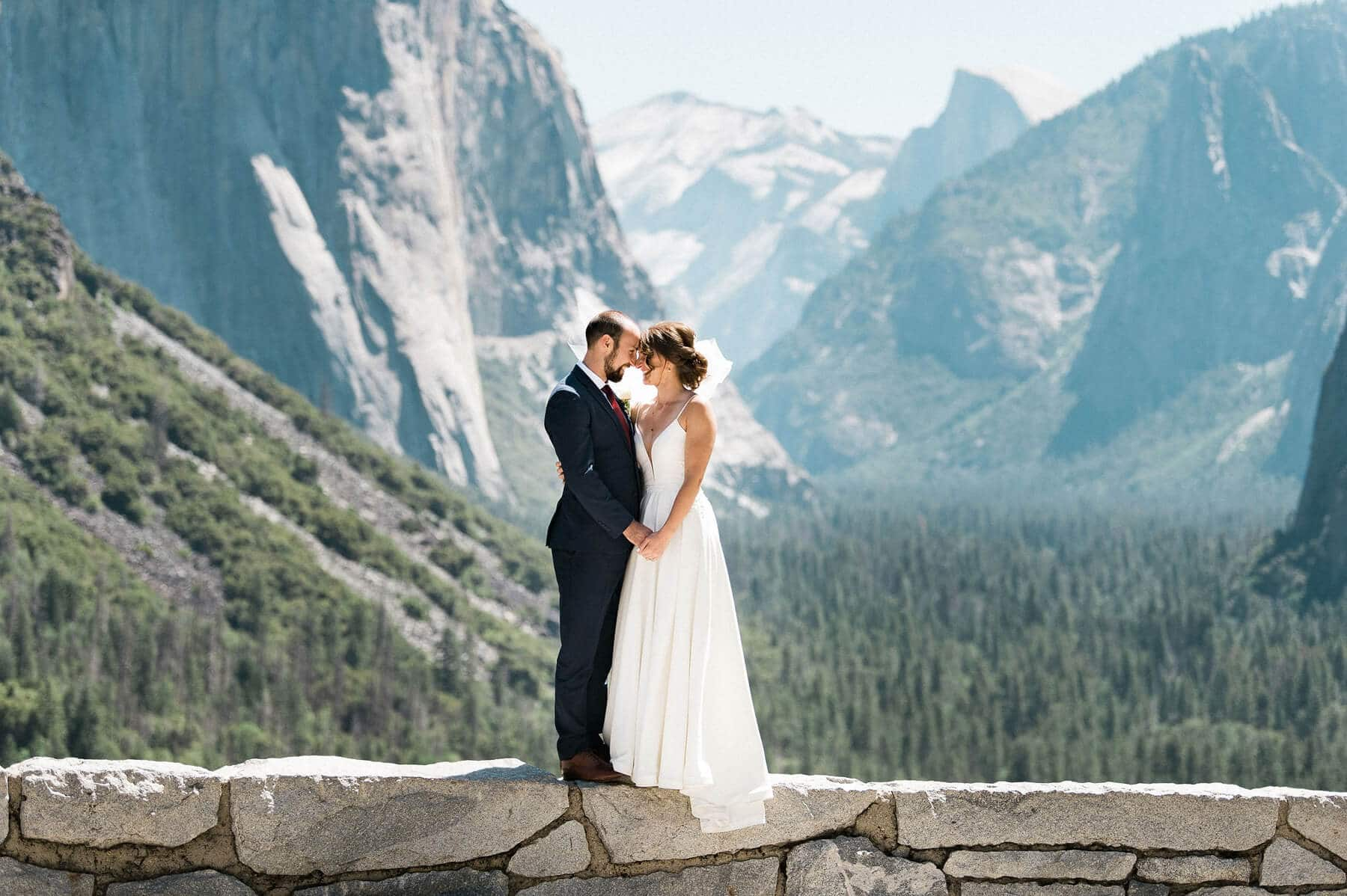 bride and groom posing on wall at tunnel view with halfdome and valley in background yosemite adventure elopement