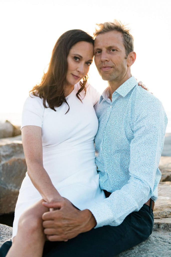 couple relaxing on jetty during ponto beach engagement photo shoot