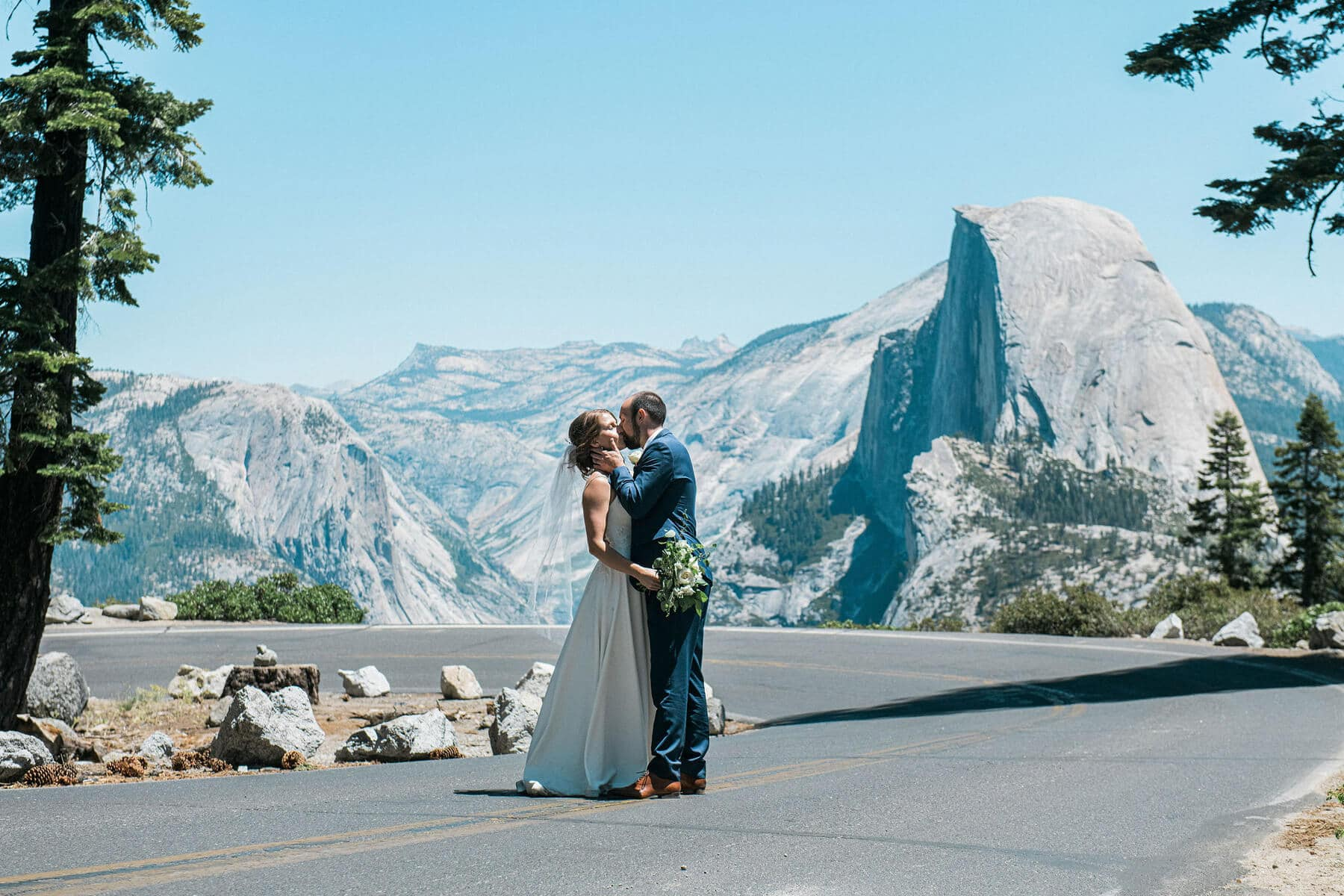 bride and groom kissing on road to glacier point with halfdome in background yosemite adventure elopement